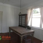Dining room with old timber table and large double hung window